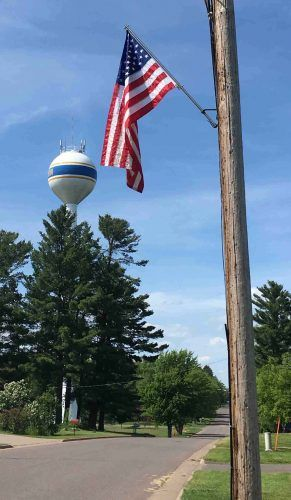 A pictures of an American flag and the New Auburn water tower